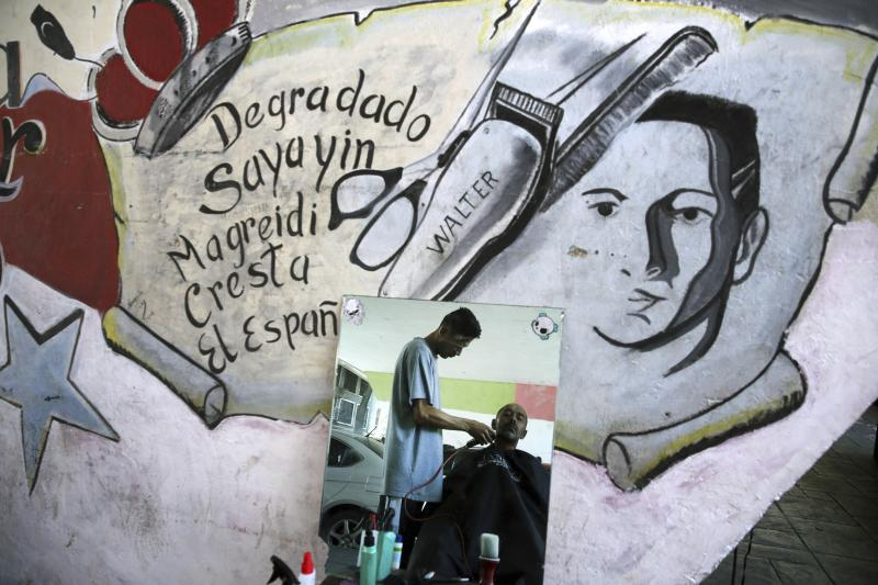 """Reflected in a mirror, Alberto Cedeno gives his client a one dollar haircut under a road bridge where he and other barbers set up shop, coined """"Bolivar Barbershop,"""" in downtown Caracas, Venezuela, Monday, May 13, 2019. The mural advertises the names of different styles of haircuts for men. (AP Photo/Martin Mejia)"""