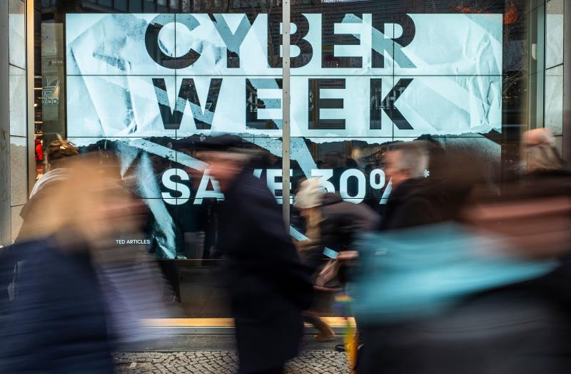 "Shoppers walk past a store advertising a so-called ""Cyber Week"" sale, in Berlin on November 23, 2018. - ""Cyber Monday"" marks the Monday after the Thanksgiving holiday in the United States, created by marketing companies to encourage people to shop online. (Photo by John MACDOUGALL / AFP) (Photo credit should read JOHN MACDOUGALL/AFP via Getty Images)"