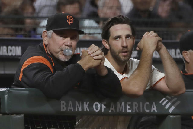 San Francisco Giants manager Bruce Bochy, left, blows a bubble while watching from the dugout with pitcher Madison Bumgarner during the seventh inning of the team's baseball game against the Oakland Athletics in San Francisco, Tuesday, Aug. 13, 2019. (AP Photo/Jeff Chiu)