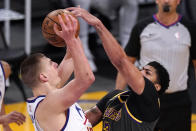 Denver Nuggets center Nikola Jokic, left, has his shot blocked by Los Angeles Lakers forward Anthony Davis during the first half of an NBA basketball game Monday, May 3, 2021, in Los Angeles. (AP Photo/Mark J. Terrill)
