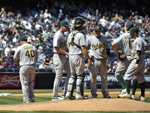 Oakland Athletics starting pitcher Bartolo Colon (40) heads to the dugout after manager Bob Melvin took him out of the game after New York Yankees designated hitter Travis Hafner hit an RBI single in sixth inning of a baseball game at Yankee Stadium on Saturday, May 4, 2013 in New York. Melvin waits on the mound with catcher John Jaso, third baseman Josh Donaldson (20), Adam Rosales (17) and second baseman Eric Sogard (28). (AP Photo/Kathy Kmonicek)