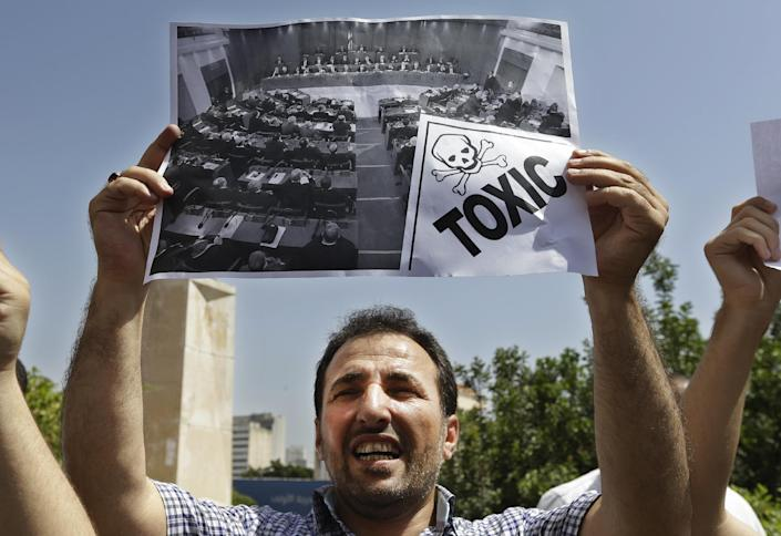 In this picture taken on May 31, 2013, a Lebanese pro-democracy protester holds up an anti-parliament poster, during a protest against the 17 months extension of the Lebanese parliament, near the parliament building in Beirut, Lebanon. Lebanese lawmakers meet in the Lebanese Parliament during a session to debate whether to extend their term 17 months, in Beirut, Lebanon. Since the current parliament was elected in June 2009, the lawmakers have met 21 times to pass 169 laws, mostly related to raise government and civil servants' salaries, receive foreign aid and amend election law that will enable their re-election. In 2013, Lebanon's lawmakers only met twice to pass two laws, one of which was to extended their mandate for 18 months. (AP Photo/Hussein Malla)