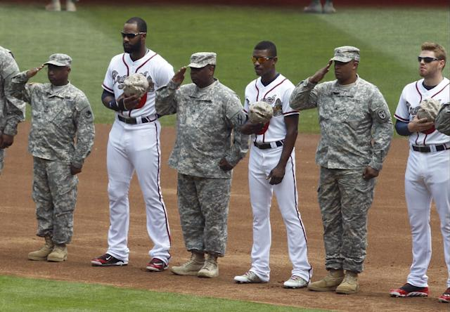 Atlanta Braves players, from left, Justin Upton, B.J. Upton and Freddie Freeman stand with soldiers during singing of the National Anthem before a MLB baseball game against the Boston Red Sox on Monday, May 26, 2014, in Atlanta, Ga. (AP Photo/Butch Dill)