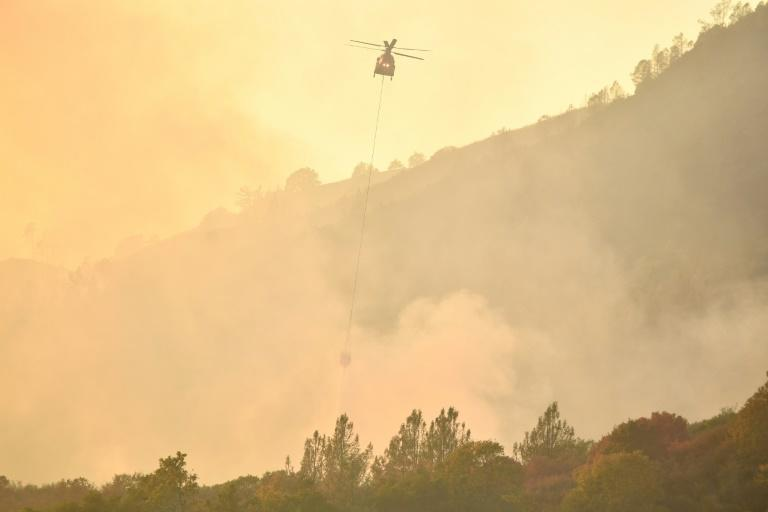 A helicopter drops water on flames in Calistoga, California