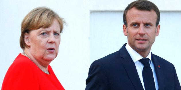 German Chancellor Angela Merkel and French President Emmanuel Macron react as they await European Commission President Jean-Claude Juncker in Meseberg, Germany, June 19, 2018. REUTERS/Hannibal Hanschke