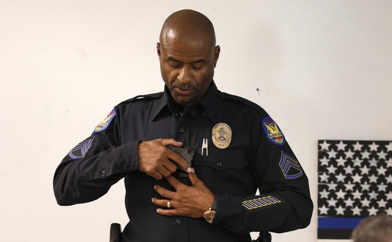 Phoenix Police Department Sgt. Kevin Johnson demonstrates the new Axon Body 2 body camera to fellow officers as another precinct gets their cameras assigned to them Wednesday, July 3, 2019, in Phoenix.  Although body-worn cameras are becoming a police standard nationwide, Phoenix was among the last big departments to adopt their widespread use. (AP Photo/Ross D. Franklin)
