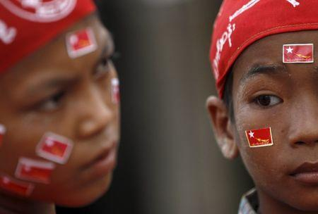 Children wear National League for Democracy (NLD) party flag stickers on their faces while waiting for Myanmar pro-democracy leader Aung San Suu Kyi during her campaign in her constituency of Kawhmu township outside Yangon September 21, 2015. REUTERS/Soe Zeya Tun