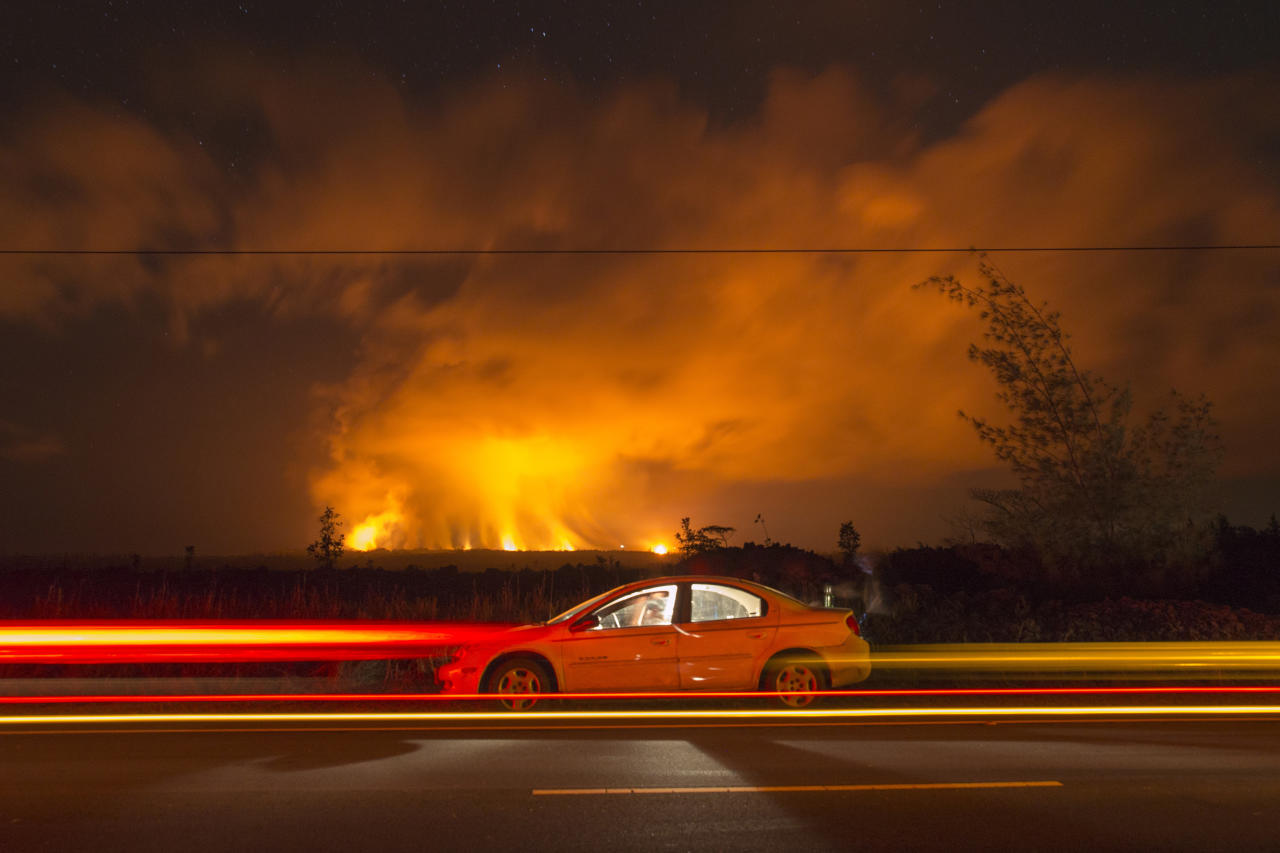 <p>A slow camera shutter speed catches the lights of cars passing spectators sitting in a car off the side of Hwy 137 to watch the volcanic activity from the Malama Ki and Lelani Estates neighborhoods, Thursday, May 17, 2018, near Pahoa, HI. (Photo: Marco Garcia/AP) </p>