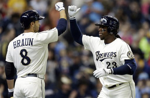 Milwaukee Brewers' Rickie Weeks (23) high-fives Ryan Braun after Weeks' two-run home run against the Chicago White Sox during the first inning of an exhibition baseball game, Saturday, March 30, 2013, in Milwaukee. (AP Photo/Jeffrey Phelps)