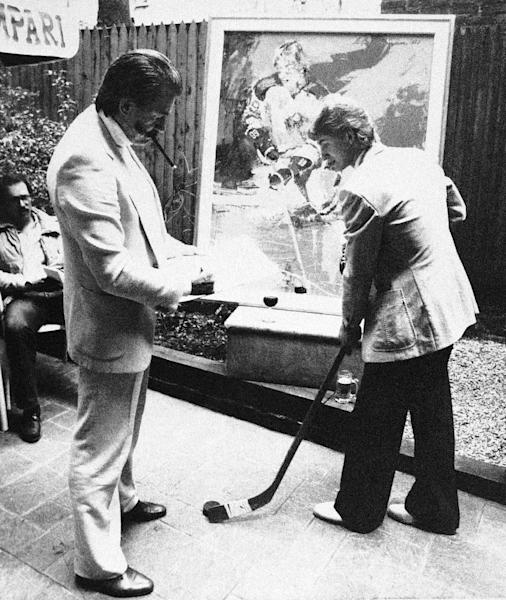 FILE - In this May 14, 1981 file photo, artist LeRoy Neiman, standing left, sketches Edmonton Oilers star forward Wayne Gretzky , right, at a restaurant in New York following the unveiling of Neiman's portrait of Gretzky, shown at rear. Neiman, who is best known for his colorful and energetic paintings of sporting events, died Wednesday, June 20, 2012 in New York. He was 91. (AP Photo/Richard Sacco, File)