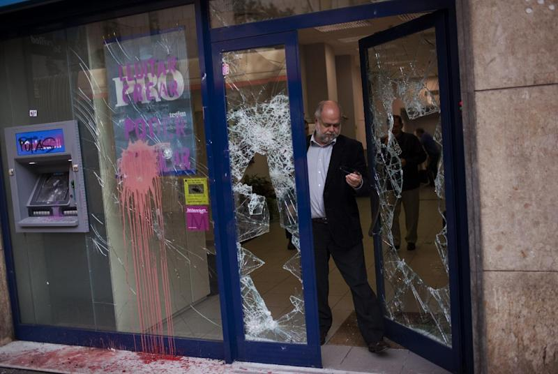 A man leaves a bank stormed by demonstrators following clashes between police and protesters after a general strike in Barcelona, Spain, Friday, March 30, 2012. The Spanish government prepared to approve on Friday a new austerity budget that hundreds of thousands protested against this week in sometimes violent demonstrations. (AP Photo/Emilio Morenatti)