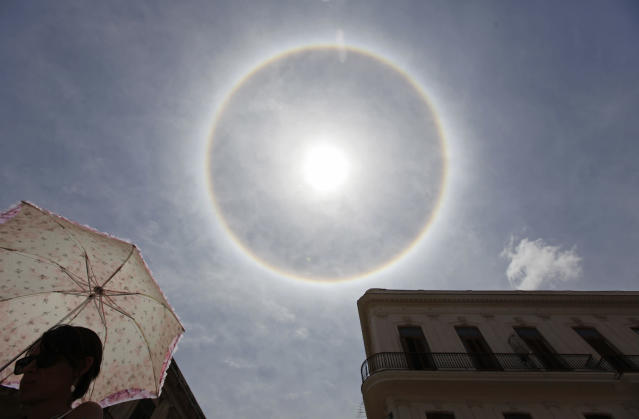 """A woman walks on a street with her umbrella as an atmospheric phenomenon known as a """"sun dog"""" is seen in the sky over Havana April 12, 2013. The rare halo around the sun is caused by the refraction of sunlight by small ice crystals in the atmosphere. REUTERS/Desmond Boylan (CUBA - Tags: SOCIETY ENVIRONMENT) - RTXYJDY"""
