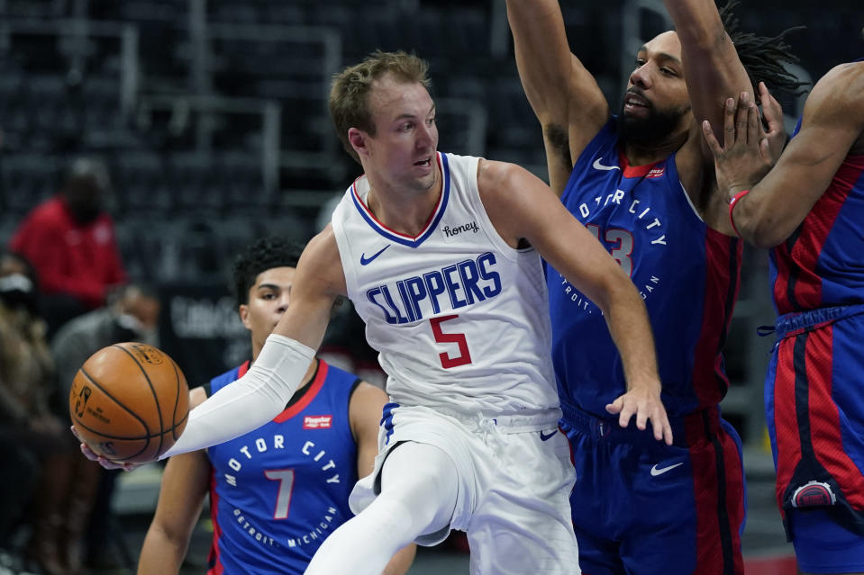 LA Clippers guard Luke Kennard (5) passes as Detroit Pistons center Jahlil Okafor (13) defends under the basket during the first half of an NBA basketball game, Wednesday, April 14, 2021, in Detroit. (AP Photo/Carlos Osorio)