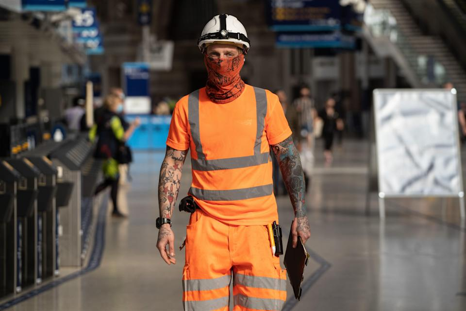 An employee wearing a face-covering walks through the concourse at Waterloo Station in London on June 15, 2020. / Credit: Niklas Halle'n / Getty