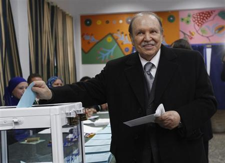 Algeria's President Bouteflika smiles during a ballot for the regional and municipal elections at a polling station in Algiers