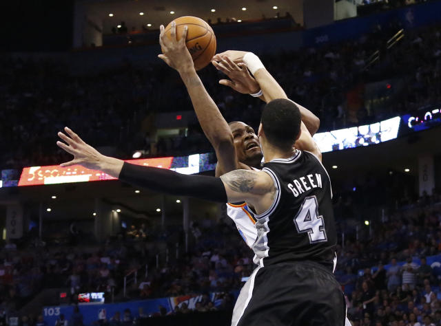 Oklahoma City Thunder forward Kevin Durant (35) is fouled by San Antonio Spurs guard Danny Green (4) on a shot during the second quarter of an NBA basketball game in Oklahoma City, Thursday, April 3, 2014. (AP Photo/Sue Ogrocki)