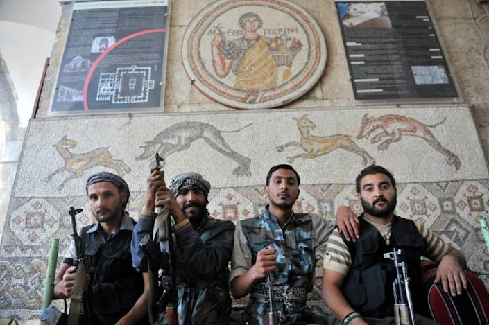 Syrian rebel fighters pose for a picture at the museum of Maaret al-Numan on October 17, 2012 (AFP Photo/BULENT KILIC)