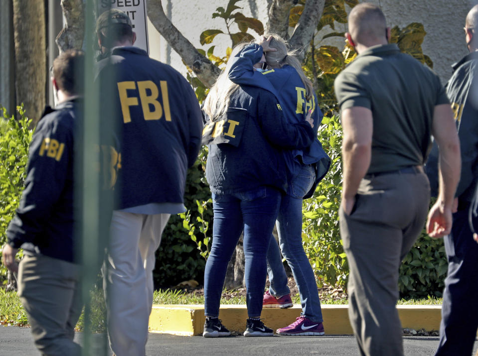 FBI agents console each other as they arrive at the Broward County Medical Examiner's Office in Dania, Fla., after two FBI agents were killed and three wounded while trying to serve a search warrant in Broward County on Tuesday Feb. 2, 2021. (Susan Stocker/South Florida Sun-Sentinel via AP)