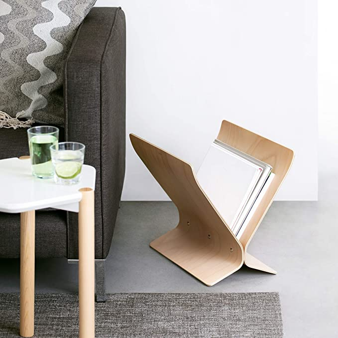 """<h3>Modern Magazine Rack</h3><br>Turn that hoard of jumbled magazines or records into an artfully organized home statement with this curvy natural wood magazine rack.<br><br><strong>Umbra</strong> Arling Magazine Rack, $, available at <a href=""""https://amzn.to/3uC3R9W"""" rel=""""nofollow noopener"""" target=""""_blank"""" data-ylk=""""slk:Amazon"""" class=""""link rapid-noclick-resp"""">Amazon</a>"""