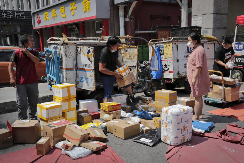 A woman wearing a protective face mask to help curb the spread of the new coronavirus waits for a delivery worker sorting out her parcel at a collection point outside an apartment in Beijing, Sunday, June 21, 2020. According to state media reports, nearly one hundred thousand delivery workers have to accept the nucleic acid testing, a countermeasure to prevent the spread of the virus in the capital city. (AP Photo/Andy Wong)