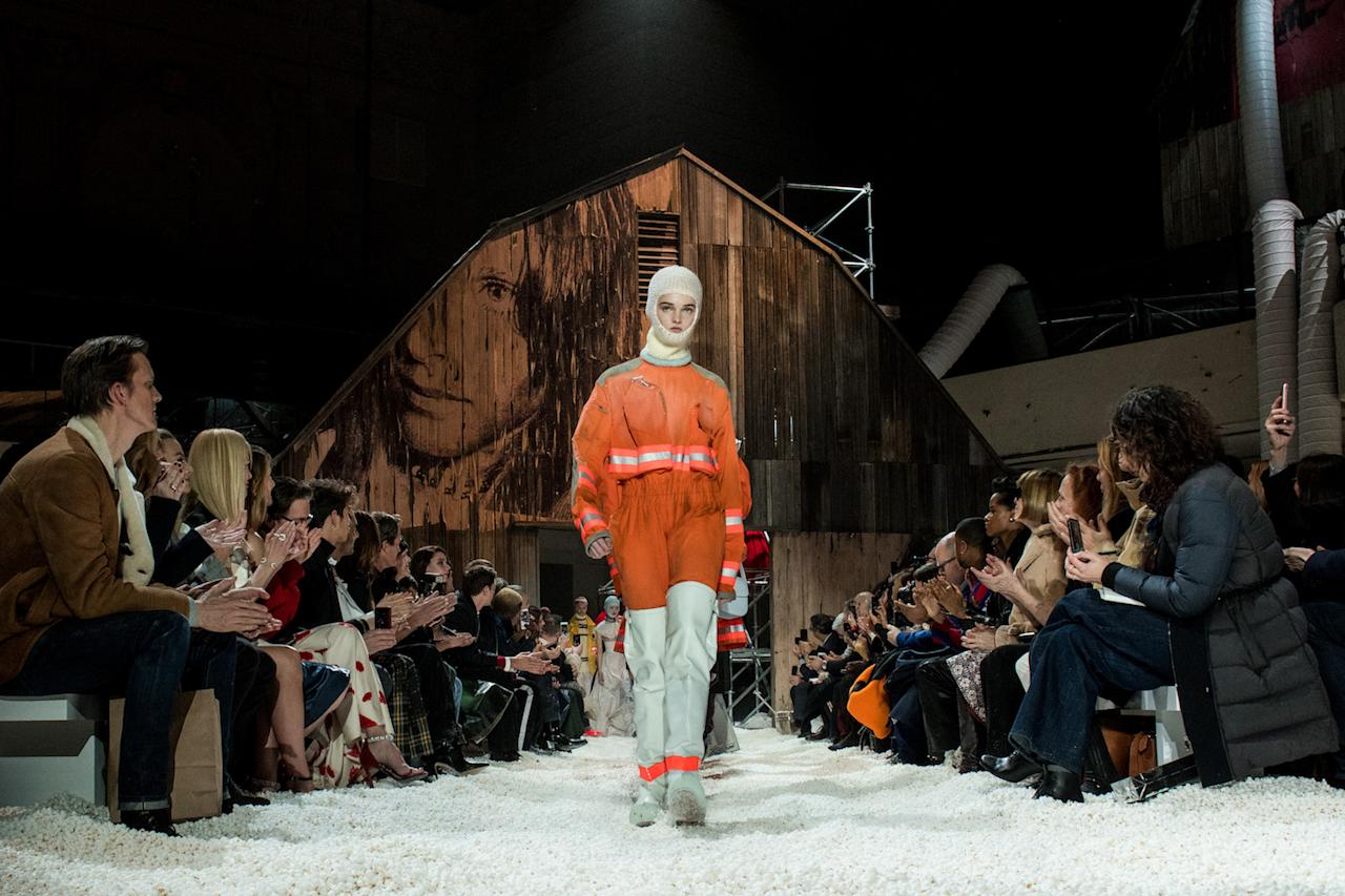 <p>Model Lulu Tenney opens the Calvin Klein fall 2018 show wearing a balaclava, an orange cropped safety jacket, pants, and thigh-high white protective boots. (Photo: Getty Images) </p>