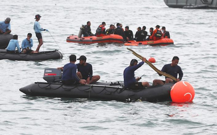 Rescuers carry debris found in the waters around the location where a Sriwijaya Air passenger jet lost contact with air traffic controllers - AP