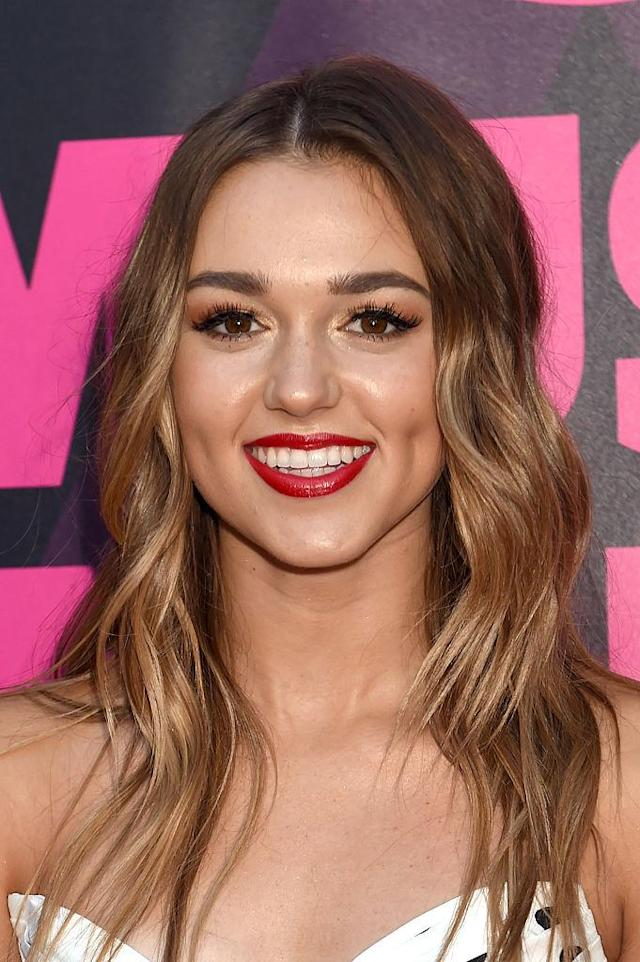 Sadie Robertston attends the 2016 CMT Music Awards wearing highlightedwavy her and bright red lipstick.