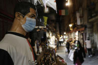 A statue of soccer star Cristiano Ronaldo, wearing a face mask, is displayed at a nativity scenes shop in San Gregorio Armeno street in Naples, Italy, Friday, Nov. 13, 2020. The regions of Campania and Tuscany were designated red zone on Friday, signaling the dire condition of a hospitals struggling with a surge of new admissions.(AP Photo/Gregorio Borgia)