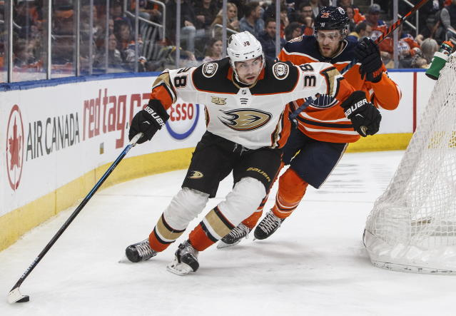 Anaheim Ducks' Derek Grant (38) skates with the puck ahead of Edmonton Oilers' Leon Draisaitl (29) during the first period of an NHL hockey game Saturday, Feb. 23, 2019, in Edmonton, Alberta. (Jason Franson/The Canadian Press via AP)