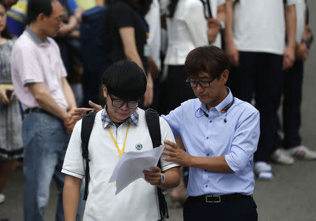 A representative of students who survived the April 16 ferry disaster cries while reading a letter as a teacher comforts him at Danwon Highschool in Ansan June 25, 2014. REUTERS/Kim Hong-Ji