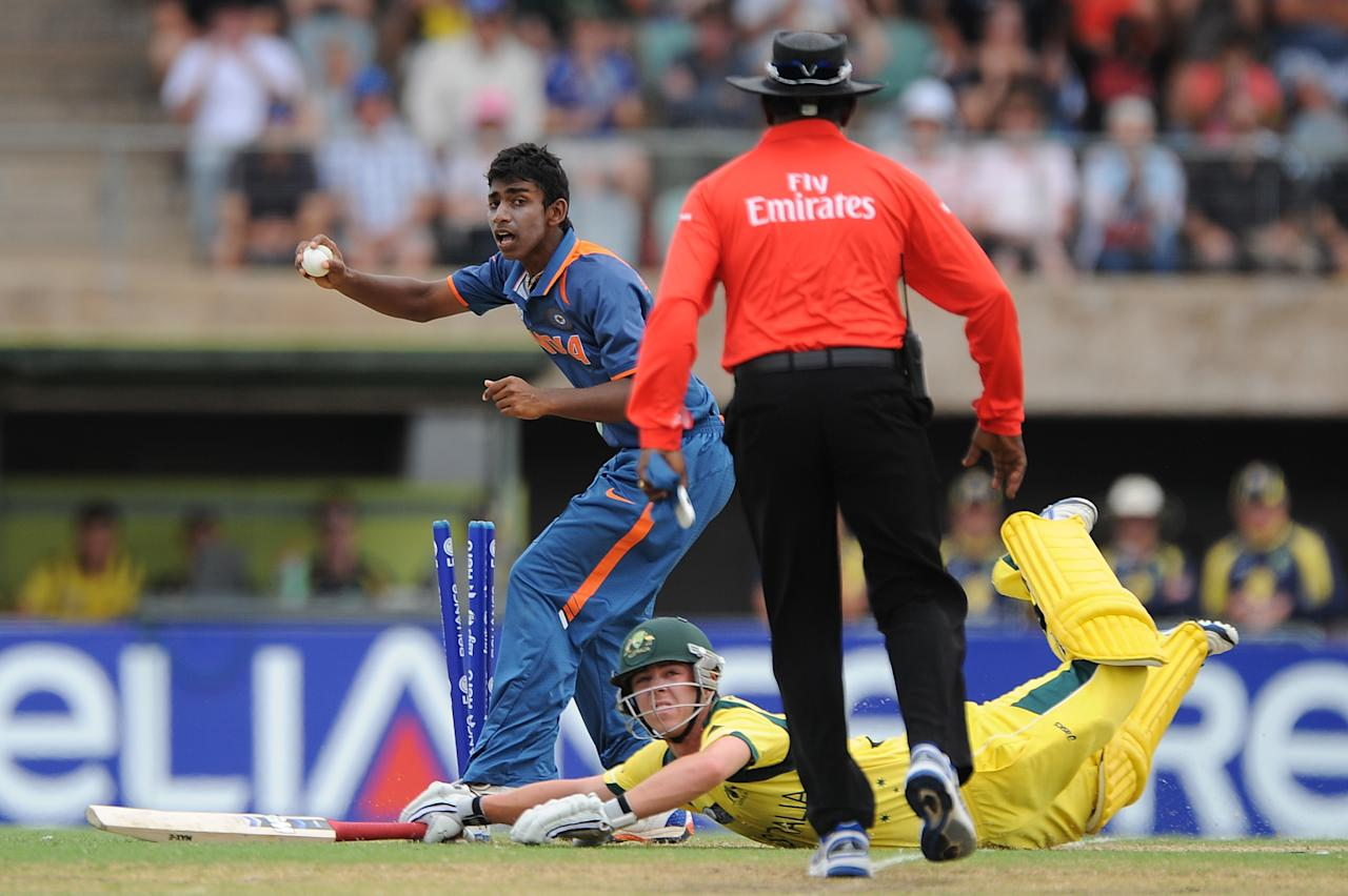 TOWNSVILLE, AUSTRALIA - AUGUST 26:  Baba Aparajith of India knocks the bails off to run out Travis Head of Australia during the 2012 ICC U19 Cricket World Cup Final between Australia and India at Tony Ireland Stadium on August 26, 2012 in Townsville, Australia.  (Photo by Matt Roberts/Getty Images)