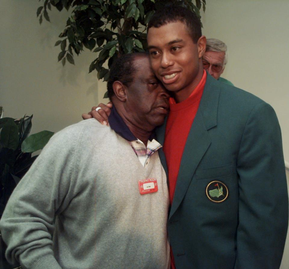 FIULE - Masters champion Tiger Woods gets a hug from Lee Elder, left, after the final round of Masters play at the Augusta National Golf Club in Augusta, Ga., in this Sunday, April 13, 1997, file photo. Elder was already 40 years old when he made history as the first Black player to tee off at the Masters, so many of his prime years squandered by the scourge of racism. (AP Photo/Amy Sancetta, File)