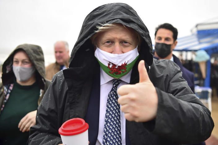 Britain's Prime Minister Boris Johnson wears a Welsh flag face mask during a visit to Barry Island, Wales, as part of the Welsh Conservative Party's Senedd election campaign, Monday, May 3, 2021. (Matthew Horwood/PA via AP)