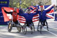Daniel Romanchuk, of Mount Airy, Md., center, winner of the pro wheelchair men's division of the New York City Marathon, is flanked by second place finisher Marcel Hug, left, of Switzerland, and third place finisher David Weir, of England, in New York's Central Park, Sunday, Nov. 3, 2019. (AP Photo/Richard Drew)