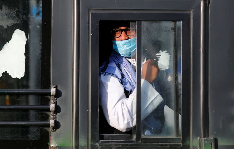 A man wearing a protective mask sits inside a bus that will take him to a quarantine facility, amid concerns about the spread of coronavirus disease (COVID-19), in Nizamuddin area of New Delhi,