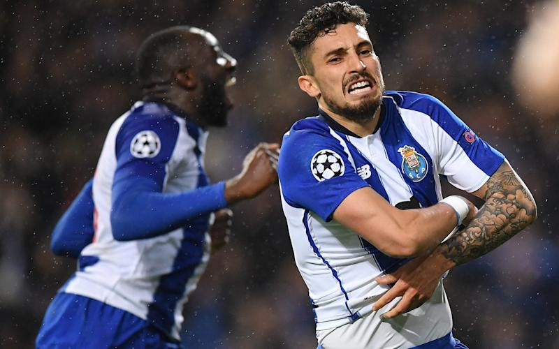 Alex Telles of Porto celebrates scoring the winning penalty in extra time during the UEFA Champions League Round of 16 Second Leg match between FC Porto and AS Roma - Stuart Franklin - UEFA/UEFA via Getty Images