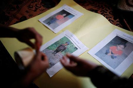 FILE PHOTO: Women make an altar with pictures of Felipe Gomez Alonzo, a 8-year-old boy detained alongside his father for illegally entering the U.S., who fell ill and died in the custody of U.S. Customs and Border Protection (CBP), at the family's home in the village of Yalambojoch, Guatemala December 27, 2018. REUTERS/Luis Echeverria