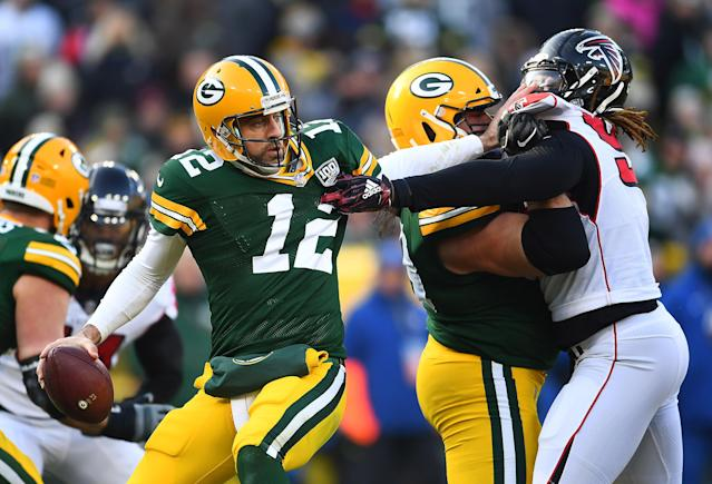 <p>Aaron Rodgers #12 of the Green Bay Packers attempts to get away from Takkarist McKinley #98 of the Atlanta Falcons during the first half of a game at Lambeau Field on December 09, 2018 in Green Bay, Wisconsin. (Photo by Stacy Revere/Getty Images) </p>