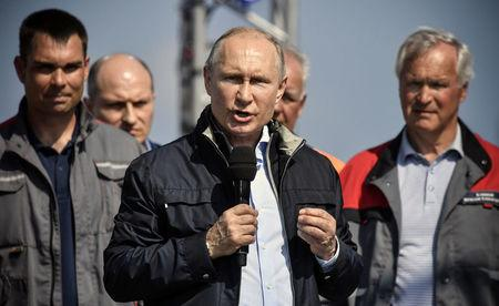 Russian President Vladimir Putin (C) delivers a speech during a ceremony opening a bridge, which was constructed to connect the Russian mainland with the Crimean Peninsula across the Kerch Strait, Crimea May 15, 2018. Alexander Nemenov/Pool via REUTERS