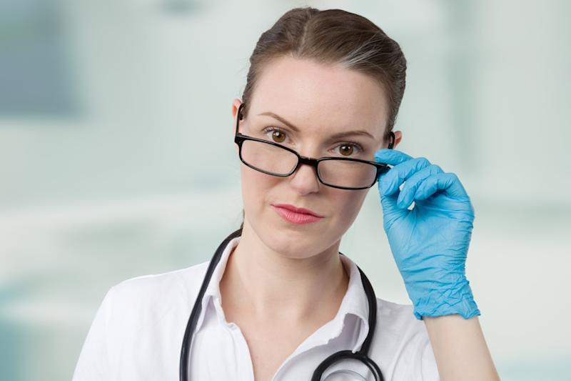 female doctor with blue medical gloves and a stethoscope looks over her glasses in front of a clinic room