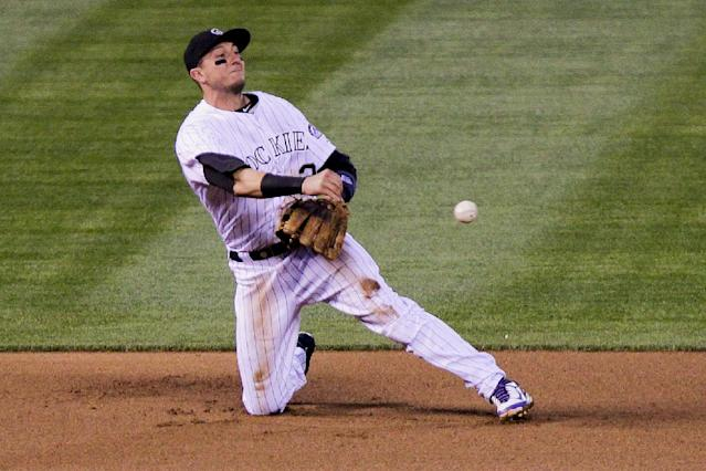 Colorado Rockies' Troy Tulowitzki throws San Francisco Giants' Brandon Belt out at second during the fourth inning of a baseball game, Tuesday, April 22, 2014, in Denver. (AP Photo/Barry Gutierrez)