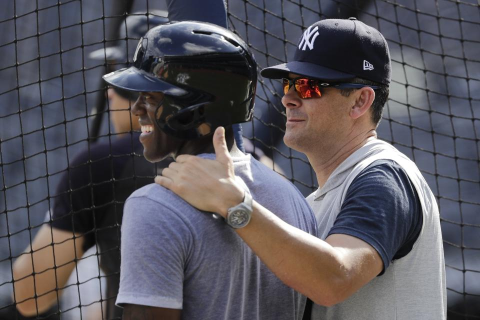 New York Yankees manager Aaron Boone, right, talks to Cameron Maybin, left, during a baseball team workout Wednesday, Oct. 2, 2019, at Yankee Stadium in New York. Yankees will host the Minnesota Twins in the first game of an American League Division Series on Friday. (AP Photo/Frank Franklin II)