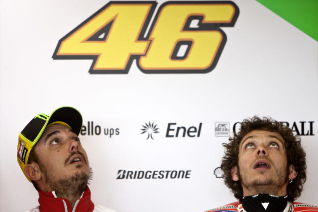 Moto GP rider Italian Valentino Rossi (R) sits in the pits with a team member (L) before the Free Practice 1 session for the Portugal Grand Prix in Estoril, on May 4, 2010. AFP PHOTO/PATRICIA DE MELO MOREIRAPATRICIA DE MELO MOREIRA/AFP/GettyImages