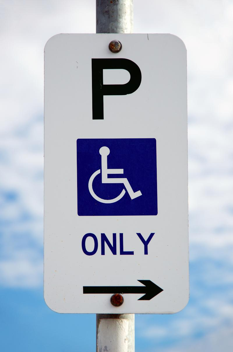 Pictured is a street sign showing it is for disabled parking only.