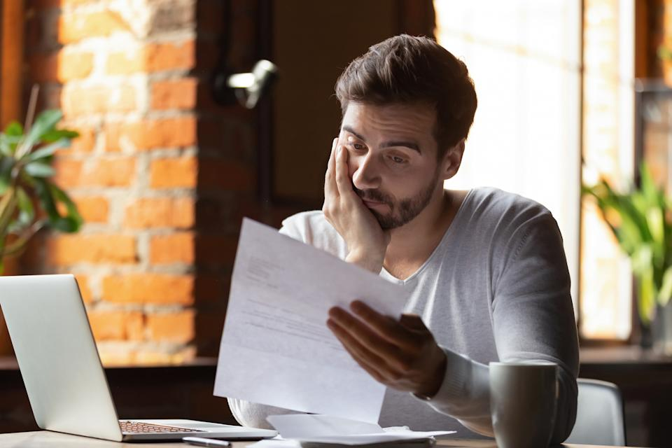 Confused frustrated young man reading letter in cafe, debt notification