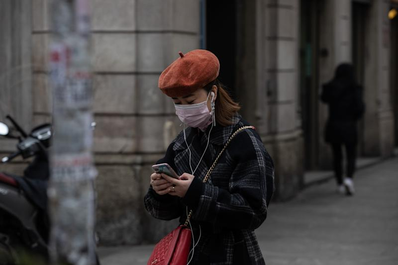 A woman, wearing a respiratory mask, uses her smartphone as she stands in the Paolo Sarpi district in Milan, Italy.