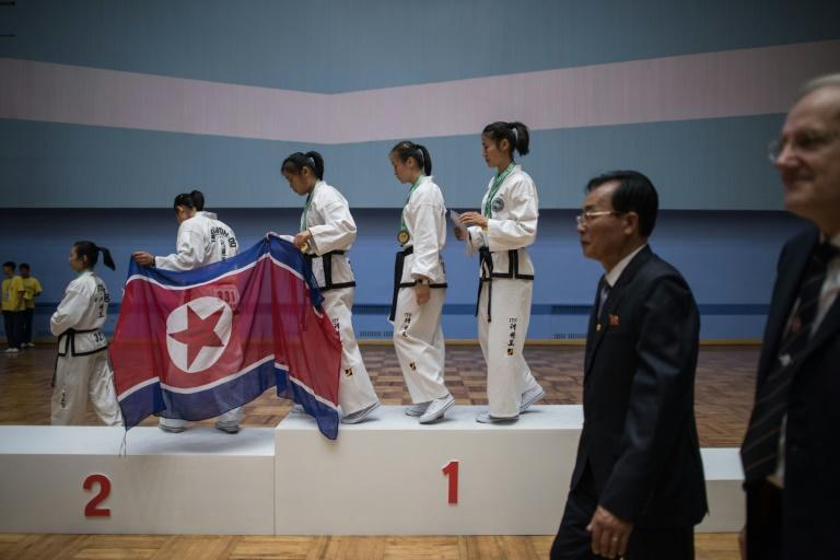 In a photo taken on September 21, 2017 team members from North Korea (C) leave the podium of during the medal ceremony of womens team event after taking first place in the 20th ITF World Taekwondo Championships in Pyongyang