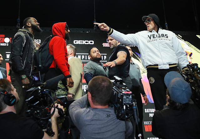 Security gets in the middle as lineal heavyweight champion Tyson Fury (R) and WBC champion Deontay Wilder got into a shoving match Wednesday at the MGM Grand Garden. (Mikey Williams/Top Rank)