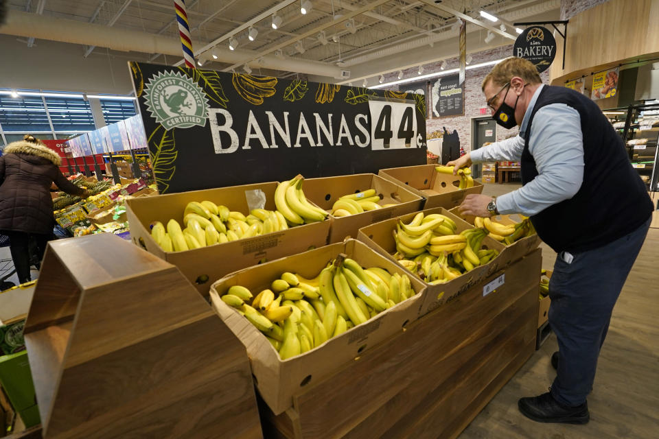 "Lidl employee Joseph Lupo, arranges bananas in the produce aisle of the market where he works, Thursday, Feb. 4, 2021, in Lake Grove, N.Y. Earlier in the day, Lupo received the first dose of the coronavirus vaccine. The German grocery chain is offering $200 to any employee who gets vaccinated as an incentive. Lupo, who fell ill with the virus in March, was elated to get his first vaccine dose. ""I never ever want to get COVID again, or see anybody else get it,"" said Lupo, 59. (AP Photo/Kathy Willens)"