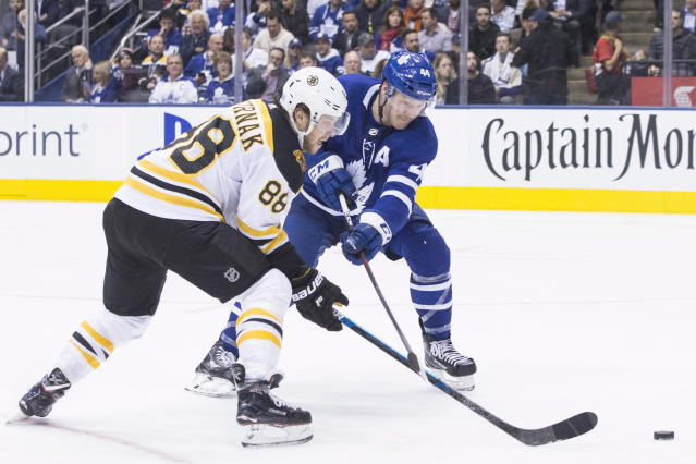 Boston Bruins' David Pastrnak (88) vies for control of the puck with Toronto Maple Leafs' Morgan Rielly (44) during third-period NHL hockey game action in Toronto, Monday, Nov. 26, 2018. (Chris Young/The Canadian Press via AP)